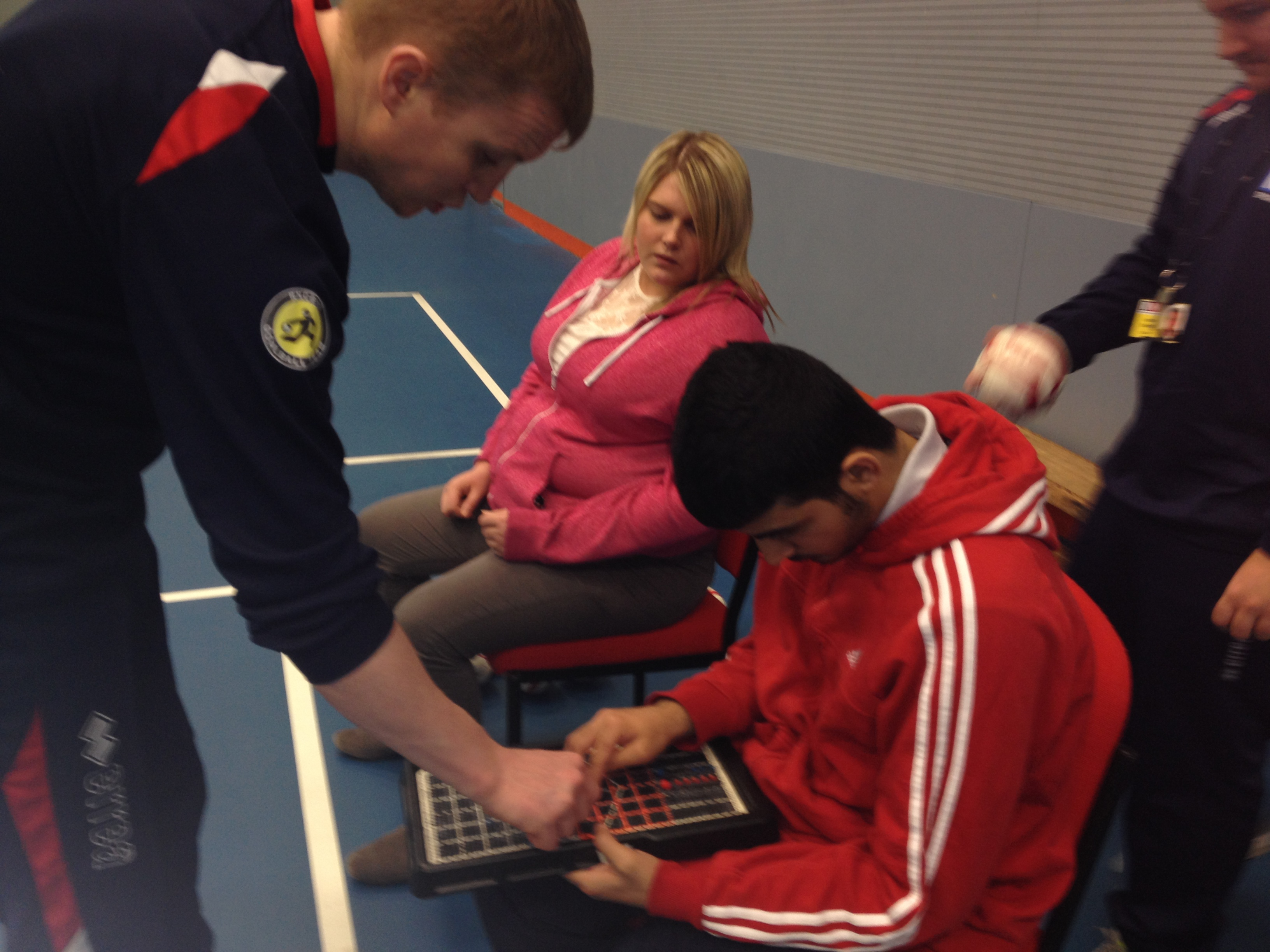 a male boccia player is plotting on the tactile map, a male teacher helps and a female player looks on